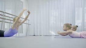 芭蕾舞团首席女演员教两个女孩做从胃肠平衡的后面exersices 股票录像