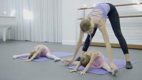 芭蕾舞团首席女演员教她小学生如何做恰当地被分裂的中间腿 股票视频