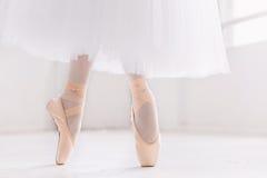 年轻芭蕾舞女演员、特写镜头在腿和鞋子,站立在pointe位置 免版税库存图片