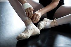 年轻芭蕾舞女演员佩带的芭蕾拖鞋 免版税库存照片