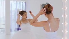 芭蕾舞女演员做她的在镜子前面的头发身分在剧院舞蹈课 影视素材