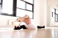 芭蕾舞女演员分裂的腿,当到达她的脚趾时 免版税库存图片