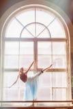 芭蕾舞女演员在一个大窗口前面跳舞 库存照片