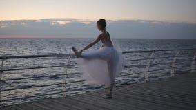 芭蕾舞女演员在散步的标志横线附近站立 她是舒展,弯曲她的在垂直的麻线的腿 影视素材