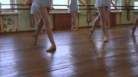 年轻芭蕾舞女演员在磨损的地板的第三个位置站立并且开始移动在旁边 股票视频