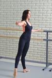 芭蕾舞女演员在纬向条花在教室,在黑紧身衣裤实践的芭蕾weared的美丽的妇女附近舒展自己 库存图片