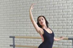 芭蕾舞女演员在纬向条花在教室,在黑紧身衣裤实践的芭蕾weared的美丽的妇女附近舒展自己 免版税库存照片