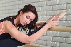 芭蕾舞女演员在纬向条花在教室,实践芭蕾的美丽的妇女附近舒展自己 免版税图库摄影