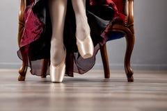 芭蕾舞女演员坐一把椅子、特写镜头在腿和鞋子 免版税库存图片