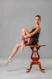 年轻芭蕾舞女演员坐木桌 免版税库存照片