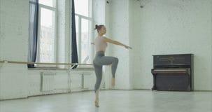 芭蕾舞女演员实践的竖趾旋转在舞蹈演播室 影视素材