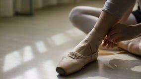 芭蕾舞女演员的脚特写镜头  为训练做准备和栓pointe鞋子的丝带芭蕾舞女演员坐地板  免版税库存照片