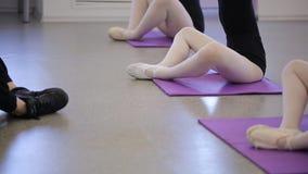 年轻芭蕾舞女演员训练与老师,舒展腿在芭蕾学校 三位小舞蹈家 股票视频