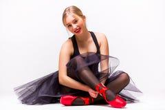 年轻芭蕾舞女演员跳芭蕾舞者画象坐地板和神色在照相机 库存照片