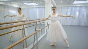 芭蕾舞短裙和pointe的芭蕾舞女演员在芭蕾机器附近订婚 股票视频
