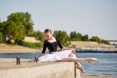 芭蕾舞短裙的亭亭玉立的芭蕾舞女演员坐城市街道 免版税库存照片