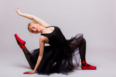 黑芭蕾舞短裙礼服做的白肤金发的美丽的女孩体操 免版税库存照片