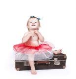 芭蕾舞短裙裙子的小女孩坐减速火箭的手提箱 免版税库存照片