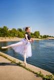 芭蕾舞短裙跳舞的亭亭玉立的芭蕾舞女演员在河岸 蔓藤花纹 免版税库存照片