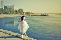 芭蕾舞短裙跳舞的芭蕾舞女演员在河岸 免版税库存图片