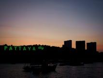 芭达亚市标志有在日落的剪影背景在pattay 库存照片