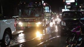 芭达亚,泰国的夜在一场强的热带暴雨以后,通过汽车和人 在街道上的大雨  股票录像