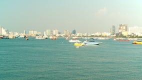 芭达亚,泰国-大约2017年3月:芭达亚在日落小船都市风景的市海滩在背景 影视素材