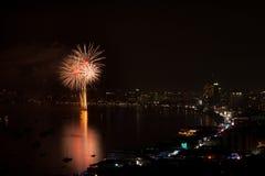 芭达亚- 11月28 :在芭达亚国际烟花节日2014 o期间,五颜六色的烟花和摩天大楼在芭达亚咆哮 免版税库存照片