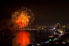 芭达亚- 11月28 :在芭达亚国际烟花节日2014 o期间,五颜六色的烟花和摩天大楼在芭达亚咆哮 库存图片