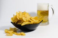 芯片用在一个杯子的啤酒在白色背景 免版税库存照片