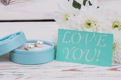 花、礼物盒有耳环的和爱消息 免版税图库摄影