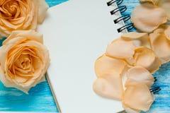 花上升了和在绿松石木背景,笔记本,大模型,文本的,妇女的天地方的瓣 免版税库存照片