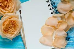 花上升了和在绿松石木背景,笔记本,大模型,文本的,妇女的天地方的瓣 图库摄影