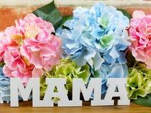 花与一个礼物盒和词妈妈的木背景的 图库摄影