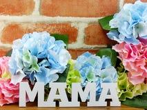 花与一个礼物盒和词妈妈的木背景的 库存照片