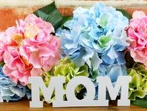 花与一个礼物盒和词妈妈的木背景的 免版税库存图片