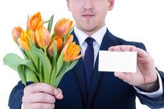 花交付-郁金香和空白的名片在男性手上 免版税库存照片
