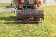 花匠操作弄脏在草草坪的通风机器 库存照片