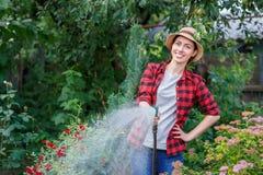 花匠浇灌的庭院 库存照片