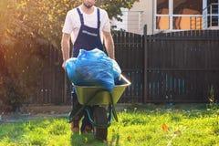 花匠滚动有袋子的一个推车叶子 清洗围场 ?? 免版税库存图片