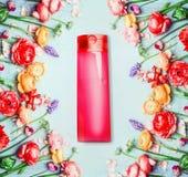 花卉化妆产品和秀丽概念 红色瓶和花在破旧的别致的背景 库存图片