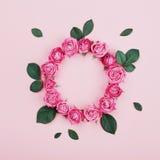 花卉框架由桃红色玫瑰制成开花,并且绿色在淡色背景顶视图离开 平的位置 时尚和创造性的构成 图库摄影