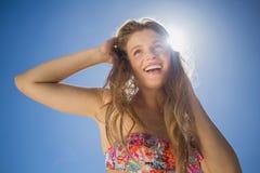 花卉比基尼泳装的美丽的微笑的金发碧眼的女人在海滩 免版税库存照片
