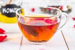 花卉红茶,蜂蜜罐头,在一张白色木桌上的瓣 免版税库存照片