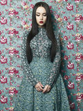 花卉背景的典雅的夫人 免版税图库摄影