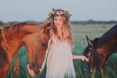 花卉花圈的微笑的女孩与马 日域热夏天麦子 免版税库存照片