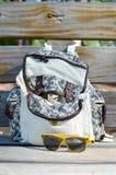 花卉设计背包和木太阳镜 图库摄影