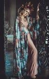 花卉颜色礼服的美丽的妇女在宫殿站立 免版税库存图片