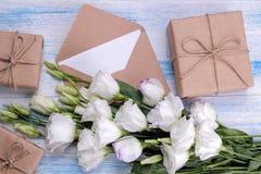 花南北美洲香草白色花束与礼物盒的和在蓝色木背景的一个信封 图库摄影