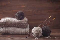 花呢与木编织针的毛纱 被编织的毛线衣 库存图片